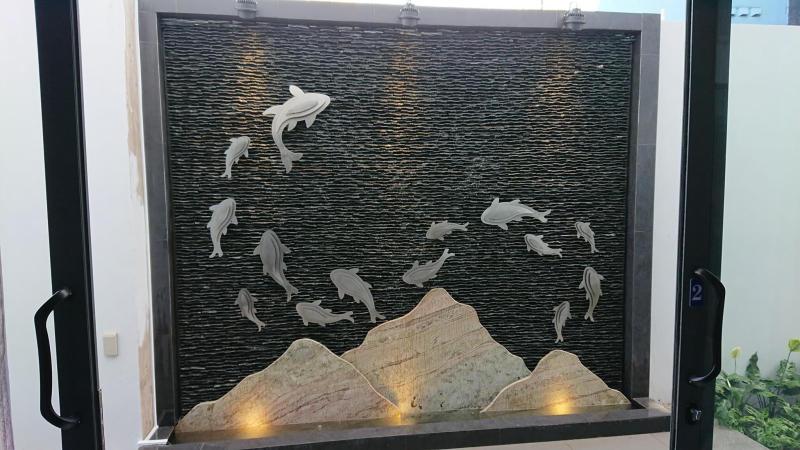 Một bức tranh nghệ thuật đàn cá bơi lội tung tăng trên nền đá suối.