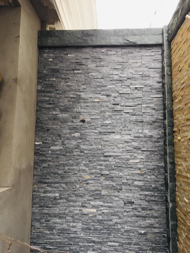 Đá ghép đen ánh kim được lựa chọn làm một mảng tường trang trí sân sau.