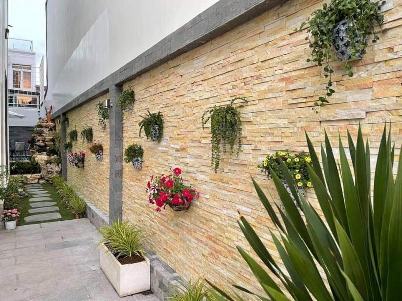 Đá ghép vàng tường rào kết hợp chậu hoa đa sắc màu khiến không gian khu vườn thêm phần rực rỡ và bắt mắt.