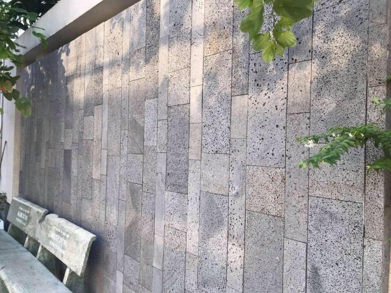 Không gian sân vườn trở nên gần gũi với thiên nhiên hơn khi dùng đá ong xám nhiều kích thước ốp tường.